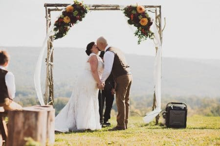 A couple kissing beneath a rustic wedding arch with colorful floral accents and tulle by Kalleco Nursery.