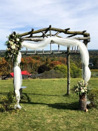 Blush floral decorations and a tulle drapeon a rustic wedding arch by Hudson Valley Florist Kalleco Nursery