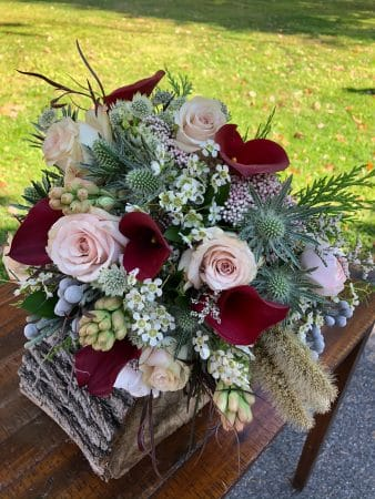 Red callalillies, blush roses, and other flowers in a rustic bridal bouquet for a Hudson Valley Farm wedding by Kalleco Nursery.